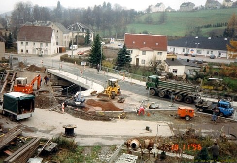 18. November 1996. Die neue Doktorbrücke ist fast fertig gestellt. Zum Zeitpunkt wurde der Verkehr einspurig durch Ampel geregelt, aber bereits über die neue Brücke geführt. Zahlreiche Restarbeiten werden erledigt. Im Vordergrund wird der Anschluss-Zipfel zu den Grundstücken Hauptstraße 61, 63 und 65 hergerichtet. Die Behelfsbrücke wird abgerissen.